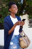 Жизнерадостная чернокожая женщина идя вниз с улицы с сотовым телефоном Стоковая Фотография
