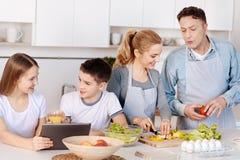 Жизнерадостная любящая семья варя обедающий совместно Стоковые Изображения