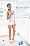 Жизнерадостная sporty модель посылая текст от ее smartphone Стоковая Фотография