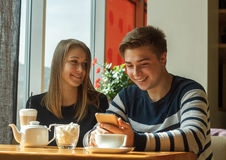 Жизнерадостное датировка пар в кафе и усмехаться стоковые фотографии rf