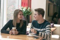 Жизнерадостное датировка пар в кафе и усмехаться стоковые фото