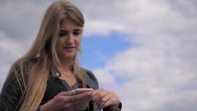 Жизнерадостное белокурое задумчивое смотрит мобильный телефон, касающий экран, портрет