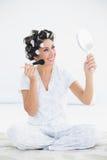 Жизнерадостное брюнет в роликах волос держа зеркало руки и applyi Стоковая Фотография