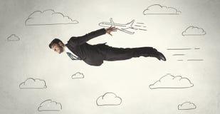 Жизнерадостное летание персоны дела между небом нарисованным рукой заволакивает бесплатная иллюстрация
