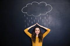Жизнерадостное заволакивание женщины от вычерченного дождя с руками над доской Стоковая Фотография RF