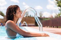 Жизнерадостное моложавое африканское заплывание девушки на курорте лета Стоковое Изображение RF