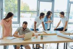 Жизнерадостное молодые люди работая в офисе Стоковые Фотографии RF