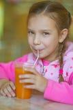 Жизнерадостное питье сока персика девушки Стоковые Фотографии RF