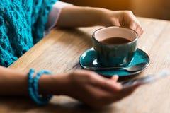 Жизнерадостное послание девушки на smartphone во время перерыва на чашку кофе Стоковые Изображения