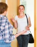 Жизнерадостное приветствие 2 женщин на двери Стоковые Изображения RF