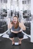 Жизнерадостное сидение на корточках женщины на масштабе веса Стоковое Фото