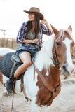 Жизнерадостное усаживание и верховая лошадь пастушкы женщины в деревне Стоковое фото RF