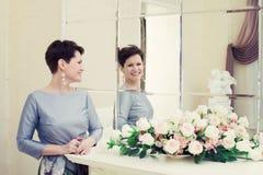 Жизнерадостной женщина постаретая серединой смеясь над в зеркале Стоковые Фото