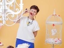 Жизнерадостной женщина постаретая серединой шаловливо сдерживая вишню Стоковая Фотография