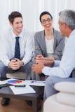 Жизнерадостные бизнесмены говоря и работая совместно на софе Стоковая Фотография