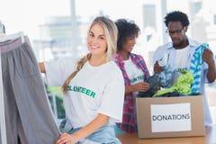 Жизнерадостные волонтеры кладя одежды в рельс одежд Стоковая Фотография RF