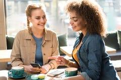 Жизнерадостные девушки говоря в магазине кондитерскаи Стоковое Изображение RF
