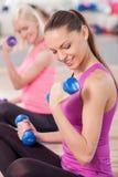 Жизнерадостные девушки пригонки делают тренировку с весами Стоковая Фотография