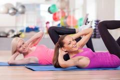 Жизнерадостные девушки пригонки тренируют в фитнес-центре Стоковые Фотографии RF