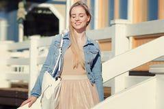 жизнерадостные детеныши девушки Молодая белокурая женщина усмехаясь в куртке джинсовой ткани Стоковое Фото