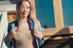 жизнерадостные детеныши девушки Молодая белокурая женщина усмехаясь в куртке джинсовой ткани Стоковое фото RF