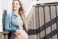 жизнерадостные детеныши девушки Молодая белокурая женщина усмехаясь в куртке джинсовой ткани Стоковые Изображения RF