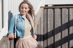 жизнерадостные детеныши девушки Молодая белокурая женщина усмехаясь в куртке джинсовой ткани Стоковые Фото
