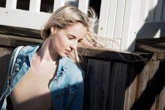 жизнерадостные детеныши девушки Молодая белокурая женщина усмехаясь в куртке джинсовой ткани Стоковая Фотография RF