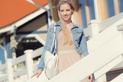 жизнерадостные детеныши девушки Молодая белокурая женщина усмехаясь в куртке джинсовой ткани Стоковые Изображения