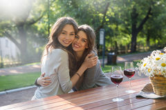 Жизнерадостные детеныши 2 женщины сидя outdoors в вине парка выпивая Стоковые Изображения