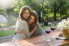 Жизнерадостные детеныши 2 женщины сидя outdoors в вине парка выпивая Стоковая Фотография RF