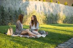 Жизнерадостные детеныши 2 женщины сидя outdoors в примечаниях сочинительства парка Стоковое Фото
