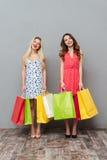 Жизнерадостные детеныши 2 друз дам держа хозяйственные сумки Стоковая Фотография