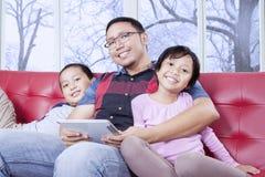 Жизнерадостные дети и папа с таблеткой усмехаясь на камере Стоковая Фотография