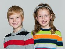 Жизнерадостные дети на серой предпосылке Стоковые Изображения