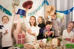 Жизнерадостные дети обменивая подарки друг с другом во время партии Стоковая Фотография RF