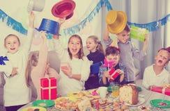 Жизнерадостные дети обменивая подарки друг с другом во время партии Стоковые Фото