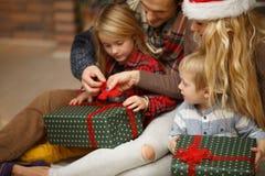 Жизнерадостные дети раскрывают подарки рождества стоковое фото