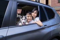 Жизнерадостные дети с щенком в автомобиле Стоковое Фото
