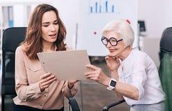 Жизнерадостные деловые партнеры обсуждая проект в офисе Стоковые Фото