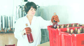 Жизнерадостные женские бутылки вина упаковки работника Стоковые Изображения