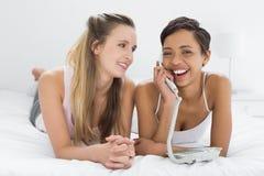 Жизнерадостные женские друзья используя телефон пока лежащ в кровати Стоковая Фотография RF