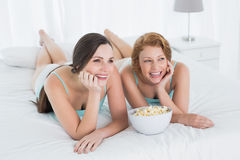 Жизнерадостные женские друзья при шар попкорна лежа в кровати Стоковые Изображения