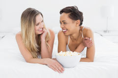 Жизнерадостные женские друзья при шар попкорна лежа в кровати Стоковая Фотография RF