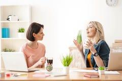 Жизнерадостные 2 женских коллеги говорят на работе Стоковое Изображение