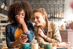 Жизнерадостные женщины говоря на таблице в кафе Стоковые Изображения RF