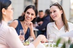 Жизнерадостные женщины говоря с коллегой на столе Стоковое Изображение RF