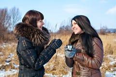 Жизнерадостные женщины переговора и горячее питье Стоковые Изображения RF