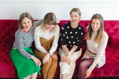 Жизнерадостные женщины сидя на кресле Стоковые Фото