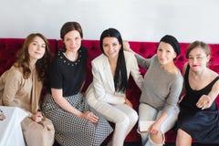 Жизнерадостные женщины сидя на кресле Стоковые Фотографии RF